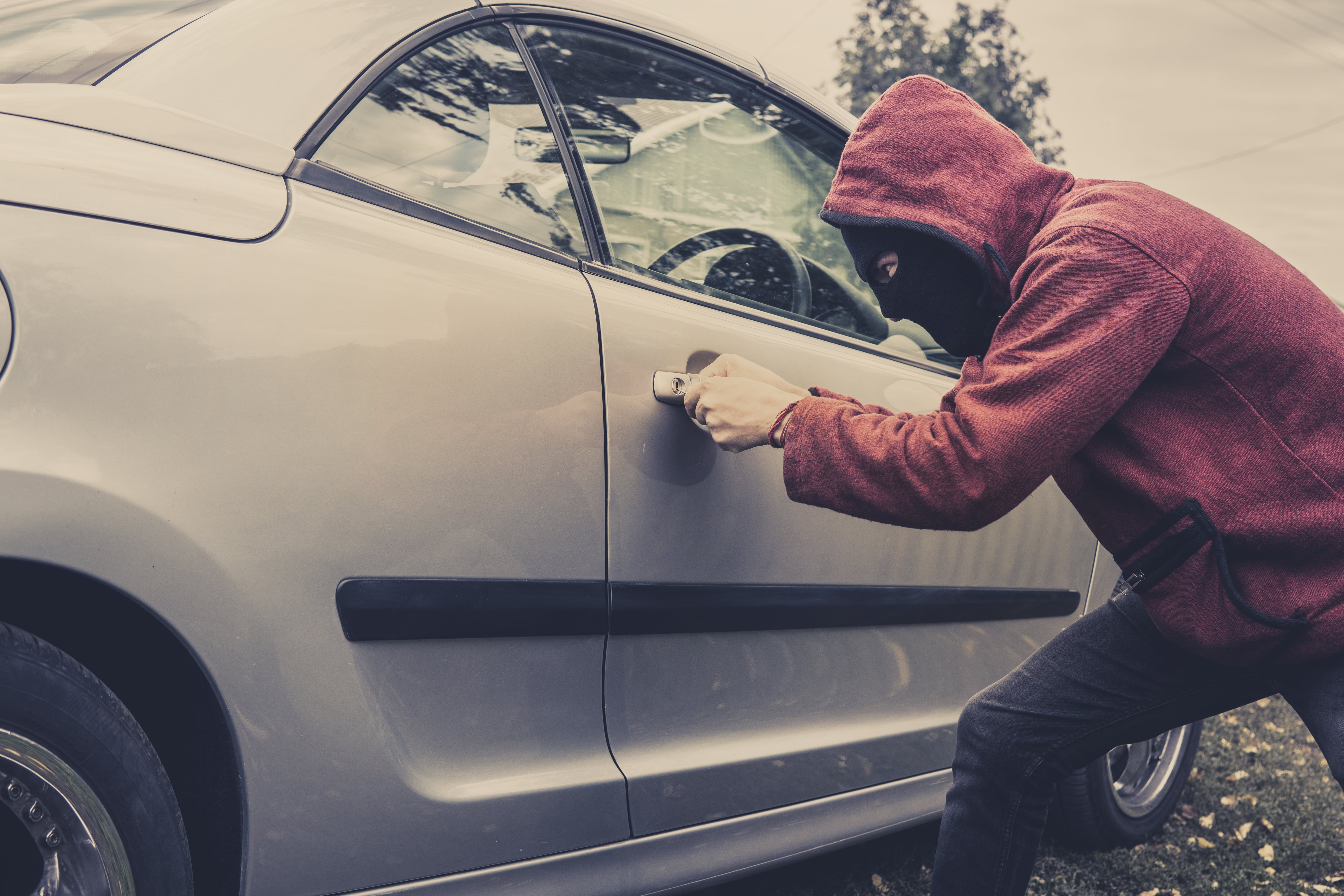 man in mask breaking into a car